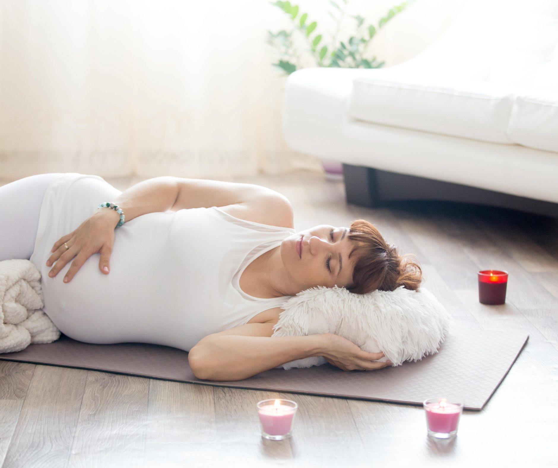 pregnant lady lying down on her side relaxing with candles